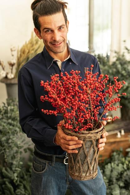 Florista experimentado sonríe y sostiene plantas rojas Foto gratis