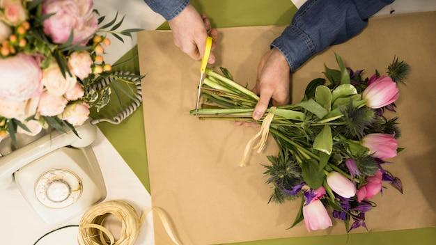 Un florista masculino que poda el tallo del ramo de flores en la floristería. Foto gratis