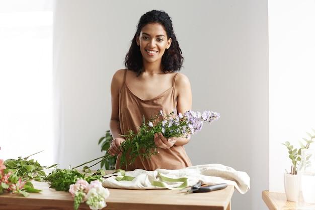 Florista de sexo femenino africano hermoso que sonríe sosteniendo las flores. pared blanca. dueño de negocio feliz de conocer clientes. Foto gratis