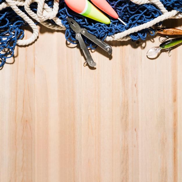 Flotador de pesca alicates; señuelos de pesca y red de pesca en superficie de madera. Foto gratis