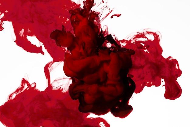 Flujo de tinta roja brillante bajo el agua Foto gratis