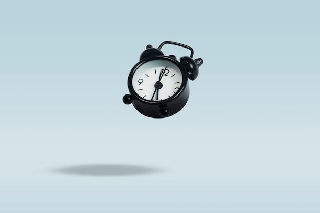 Flying black despertador sobre un fondo azul. levitación. concepto de gestión del tiempo Foto Premium
