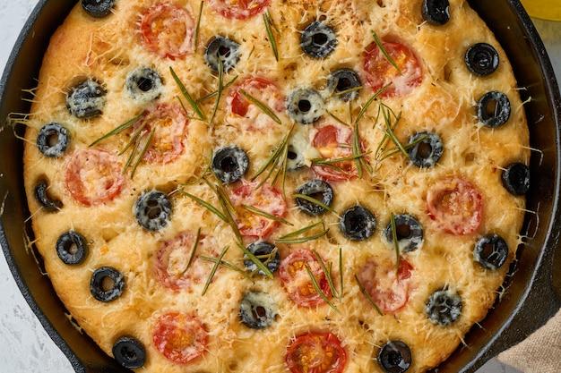 Focaccia, pizza en sartén. cerrar pan plano italiano con tomate, aceitunas y romero Foto Premium