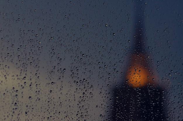 Foco parcial de la gota de lluvia en la ventana de cristal en la estación del monzón con la pagoda borrosa del fondo del templo. Foto Premium