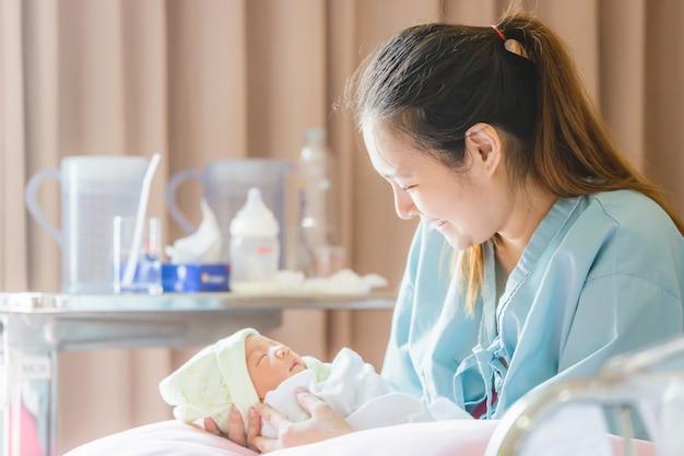 Foco selectivo de la madre asiática feliz que mira al bebé recién nacido que duerme a disposición en el hospital Foto Premium