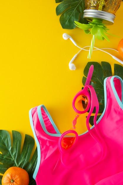 Fondo abstracto de verano. traje de baño rosa y tarro de piña para jugo. Foto Premium