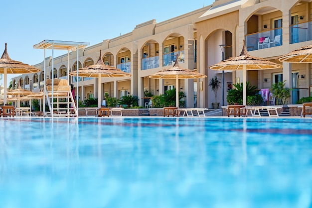 Fondo de agua en la piscina azul, superficie del agua con un reflejo del sol Foto Premium
