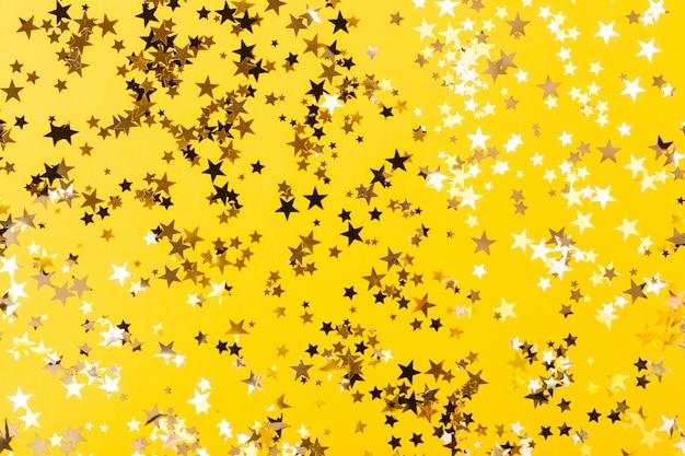 Fondo amarillo confeti en forma de estrella Foto Premium