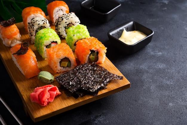 El fondo asiático de la comida con la tetera y el sushi negros del hierro fijó en la placa de madera en la tabla de piedra negra Foto Premium