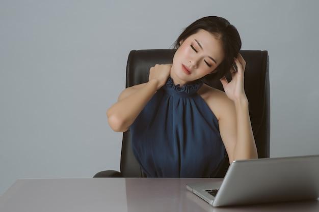 Fondo asiático de la oficina del dolor de hombro y del dolor de espalda de la mujer de negocios Foto Premium