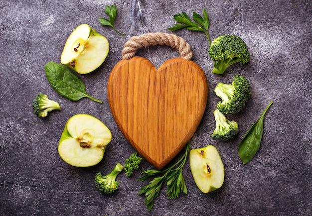 Fondo de comida verde con tablero de madera en forma de corazón Foto Premium