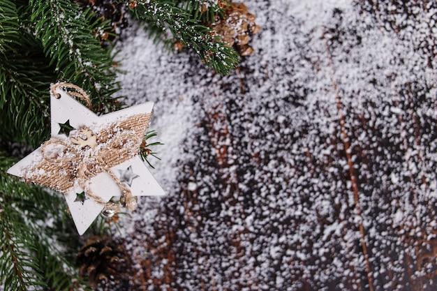 Fondo de concepto de navidad, decoración de estrellas hechas a mano y verdes árboles de navidad en una mesa de madera, salpicada de nieve blanca Foto Premium