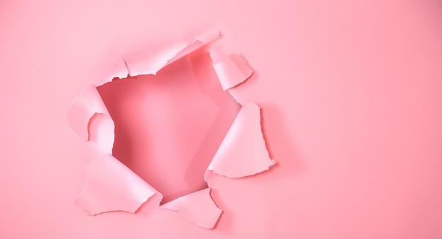 El fondo es rosa con un agujero para publicidad Foto gratis