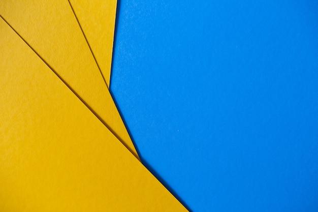 Fondo geométrico coloreado de la textura del papel azul y amarillo Foto gratis