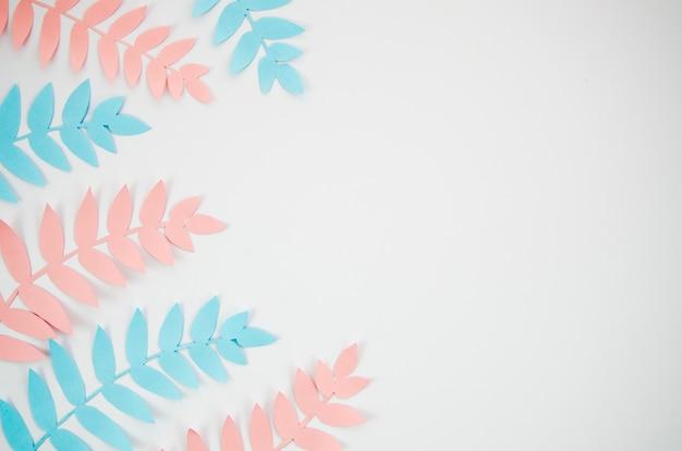 Fondo gris espacio de copia con follaje rosa y azul Foto gratis