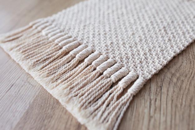 Fondo de macramé beige hecho a mano. textura macramé, tejido ecológico y moderno. alfombra de macramé en mesa de madera Foto Premium