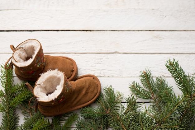 Fondo de madera de invierno de bebé con árbol de navidad y bootsm Foto Premium