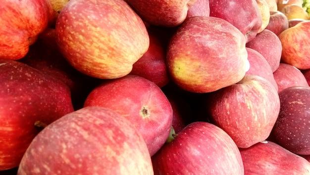 Fondo de manzanas crujientes de miel roja fresca escogida en la temporada de cosecha colocada en un mercado o bazar para la venta Foto Premium