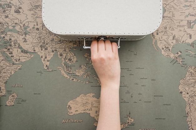 Fondo de mapa del mundo con mano agarrando una maleta Foto Premium