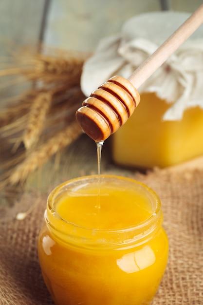 Fondo de miel dulce miel en tarro de cristal sobre fondo de madera. Foto Premium