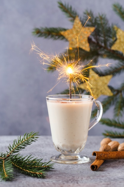 Fondo de navidad con cajas de regalo, estrellas, decoración festiva, abeto, ramas de canela, bebida de ponche de huevo caliente. Foto Premium