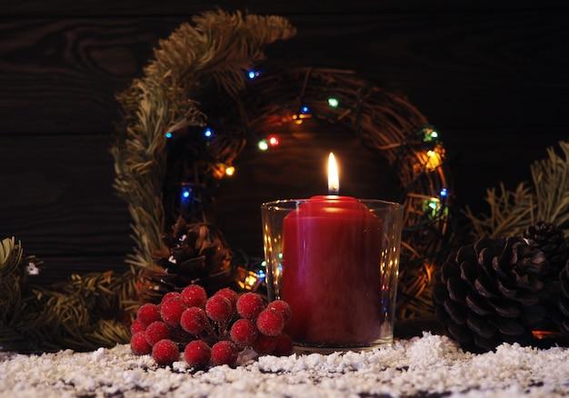 Fondo de navidad o adviento con una vela encendida en la nieve, decorado con ramas de abeto y adornos Foto Premium