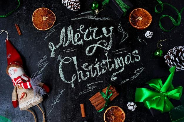 Fondo de navidad con las palabras feliz navidad, naranja seca, piña blanca, bolas de árbol de navidad verde Foto Premium
