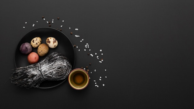 Fondo oscuro con un plato de huevos y pasta Foto gratis