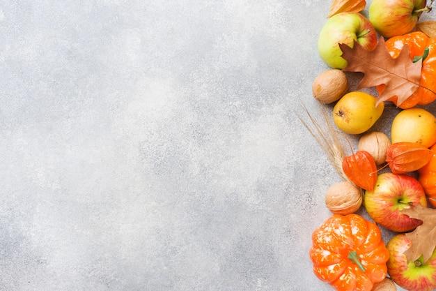 Fondo de otoño con hojas amarillas, calabazas, manzanas, peras y nueces Foto Premium