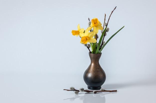 Fondo de pascua fondo de primavera con narcisos amarillos y ramas de sauce en el florero. Foto Premium