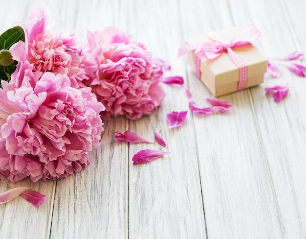 Fondo con peonías y caja de regalo Foto Premium