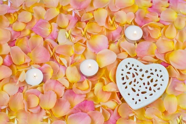 Fondo de pétalos de rosa color de rosa, corazón de cerámica tracería y tres velas Foto Premium