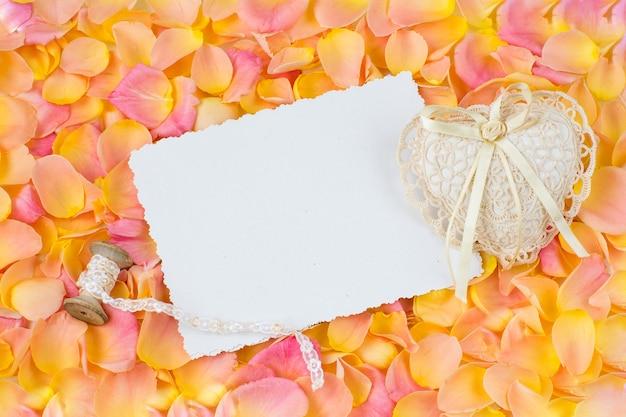 Fondo de pétalos de rosa rosa, hoja de papel, corazón de encaje y cinta Foto Premium