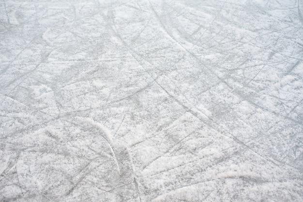 Fondo de piso de una pista de hielo congelado con marcas de patines, con nieve blanca durante el invierno. Foto Premium