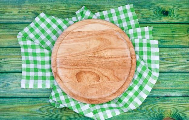 Fondo de pizza. tabla de cortar redonda sobre manteles a cuadros verdes en la mesa, vista desde arriba Foto Premium