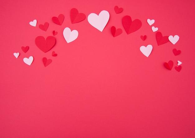 Fondo de san valentín con corazones de papel rosa y rojo Foto gratis