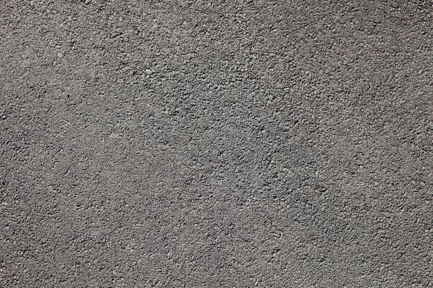 Fondo de textura de pavimento de asfalto gris oscuro liso con pequeñas rocas Foto Premium