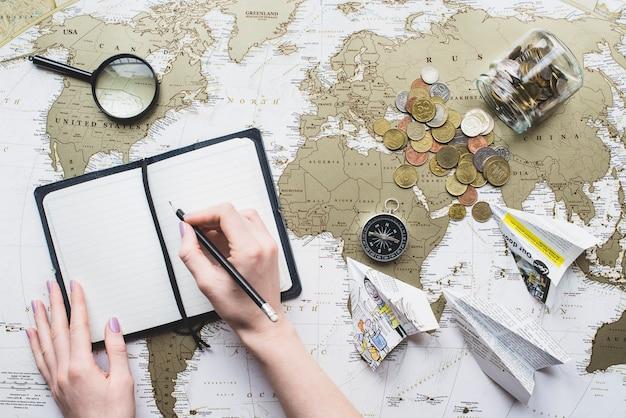Fondo de viaje con manos escribiendo en un cuaderno en blanco Foto gratis