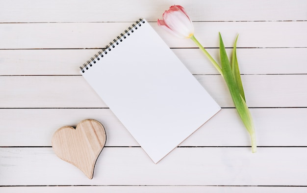Forma de corazón de madera; bloc de notas de espiral en blanco y tulipán en mesa de madera Foto gratis