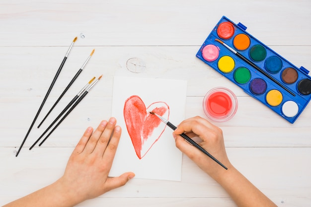 Forma de corazón de pintura de mano de la persona con pincelada de color de agua roja sobre mesa de madera Foto gratis