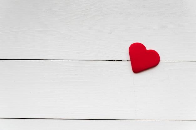 Forma de corazón rojo suave en tablón de madera blanco Foto gratis