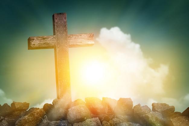 Forma cruzada de madera en la colina rocosa en la puesta del sol con el fondo del cielo azul y de las nubes, concepto del símbolo de la religión Foto Premium
