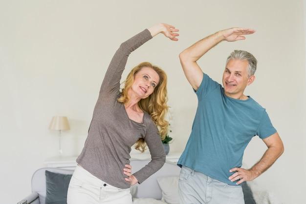 Forma pareja senior haciendo ejercicio en interiores Foto gratis