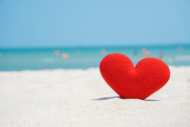 La forma roja del corazón en la arena de la playa, ama el mar Foto Premium