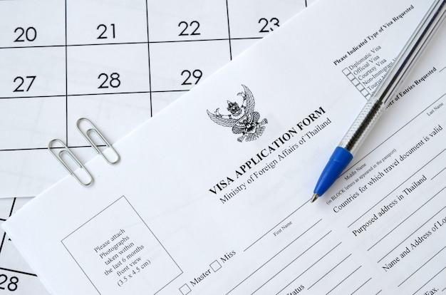 Formulario de solicitud de visa de tailandia y bolígrafo azul en la página de calendario de papel Foto Premium