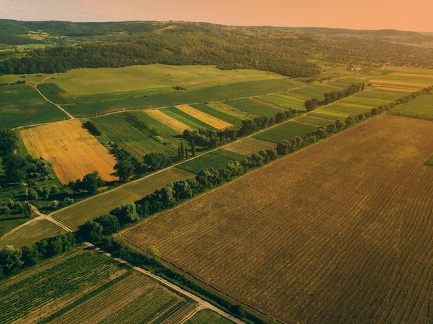 Foto aérea de drone con hermoso paisaje farmlamnd al atardecer en atmósfera rural Foto Premium
