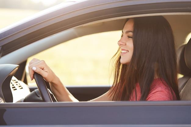 Foto de una alegre y alegre conductora morena mira felizmente el parabrisas Foto gratis