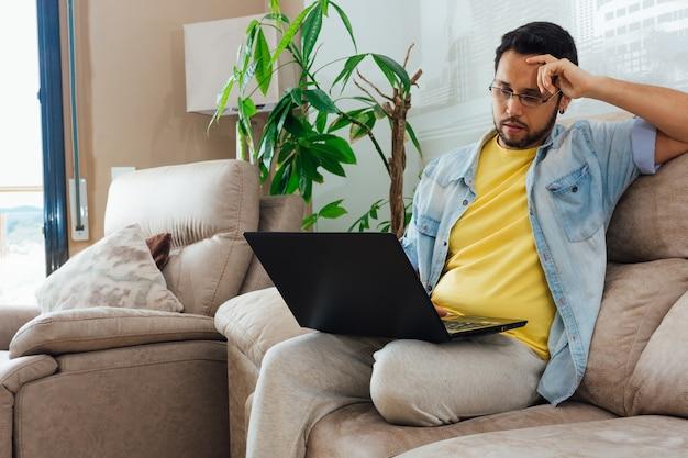 Foto de un apuesto hombre hispano sentado en un sofá y usando una computadora portátil Foto gratis
