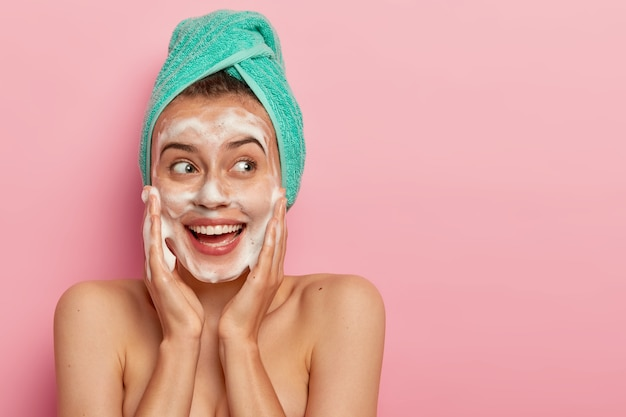 Foto de cabeza de una encantadora modelo femenina sonriente que toca las mejillas, mira a un lado, se lava la cara con una pompa de jabón, tiene el cuerpo desnudo, usa una toalla suave turquesa en la cabeza, posa sobre una pared rosada, copia espacio para promoción Foto gratis