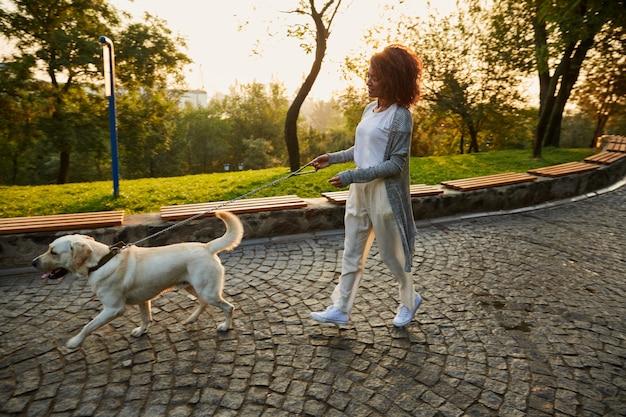 Foto de cuerpo entero de bastante saludable jovencita caminando por la mañana en el parque con perro Foto gratis